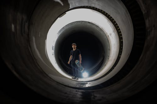 Man in Black Shirt and Blue Denim Jeans Standing on Tunnel