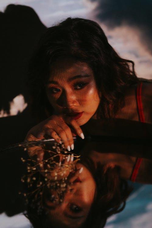 Dreamy Asian woman reflecting in mirror