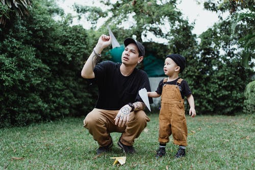 Man And Child Throwing Paper Airplanes