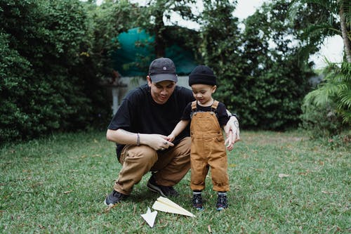 Man Holding a Child on a Grass Lawn