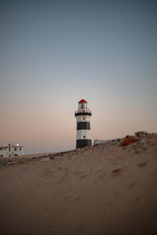 White and Black Lighthouse on Beach