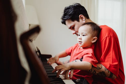 Boy in Red Crew Neck T-shirt Playing Piano