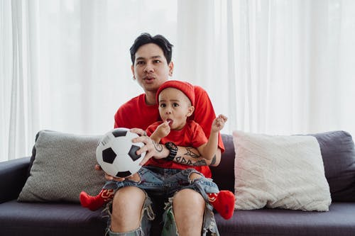 Boy in Red Shirt Sitting on Couch