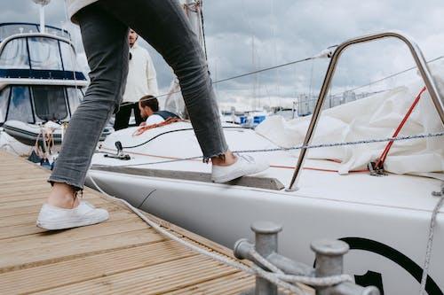 Person In Grauen Hosen Und Schwarzen Socken, Die Auf Weißem Boot Stehen
