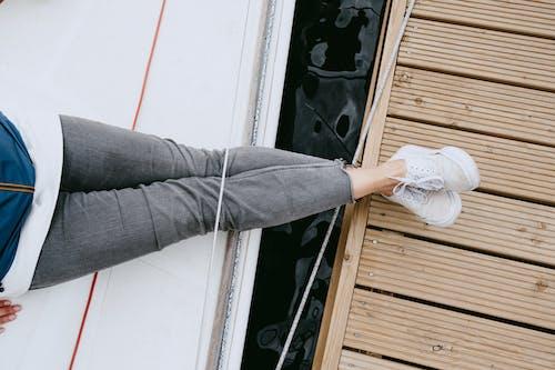 Person In Grauen Jeans Und Weißen Turnschuhen, Die Auf Weißer Holztür Stehen