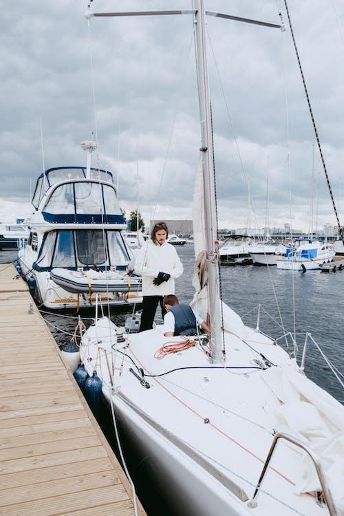 Mann Im Weißen Hemd Und In Der Schwarzen Hose, Die Auf Weißem Und Blauem Boot Sitzen