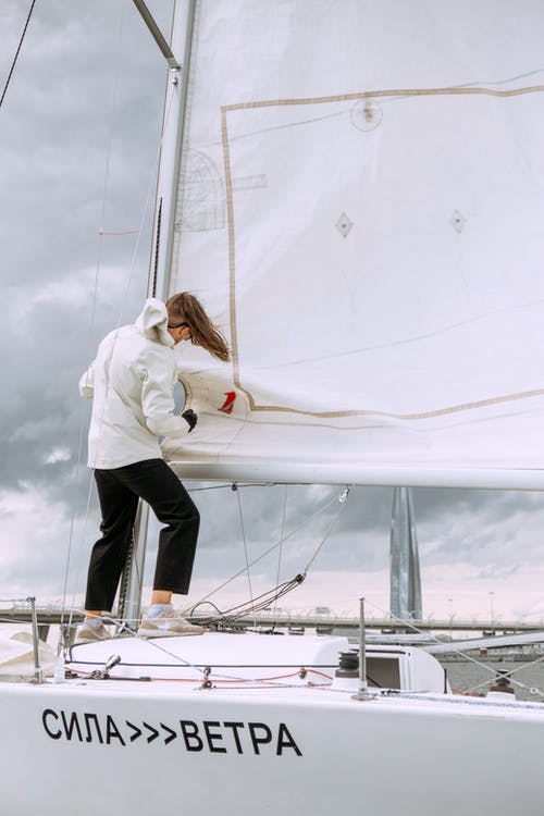 Woman in White Long Sleeve Shirt and Black Pants Standing on White Boat