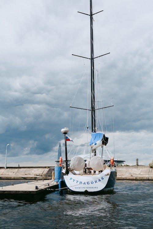 Weißes Und Blaues Boot Auf Dock Unter Bewölktem Himmel