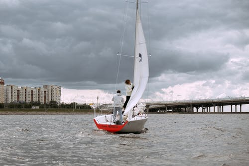 Man in White Shirt Riding Red and White Sail Boat on Sea