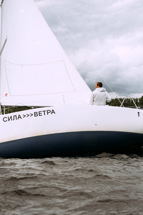 Man in White Robe Sitting on White Sailboat