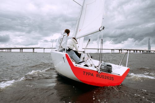 Man in White Shirt and Black Pants Riding on Red and White Boat