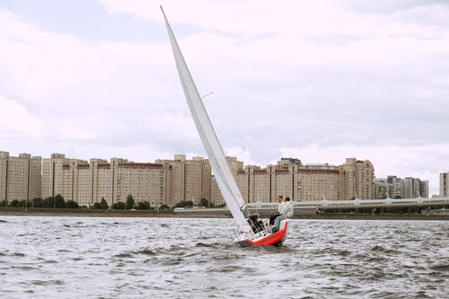 Red and White Sail Boat on Water Near City Buildings