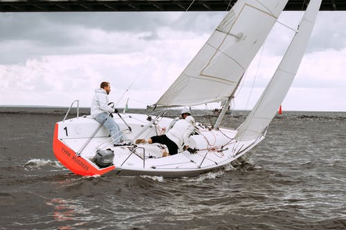 Man in White Dress Shirt and Red Pants Sitting on White and Red Sail Boat during