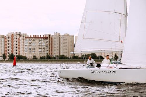 Man in White Shirt Riding White Sail Boat