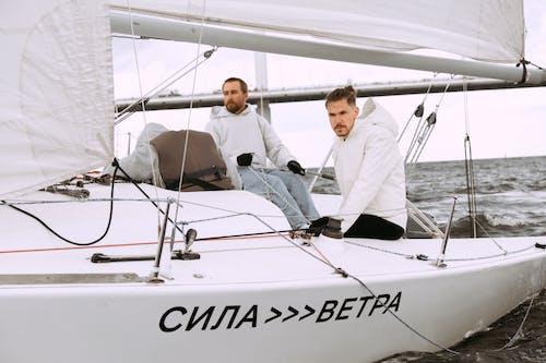 Man in White Shirt Sitting on White Boat