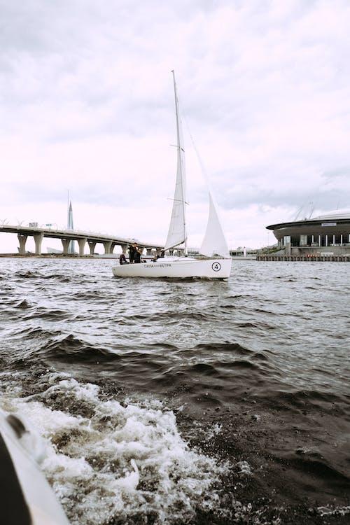 Perahu Putih Di Laut Dekat Jembatan Di Bawah Langit Berawan