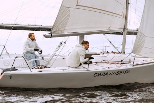 Man in White Shirt Sitting on White Sail Boat