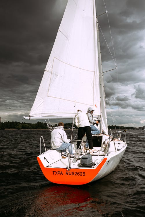 Man in White Shirt and Black Pants Riding on Orange and White Sailboat on Sea during
