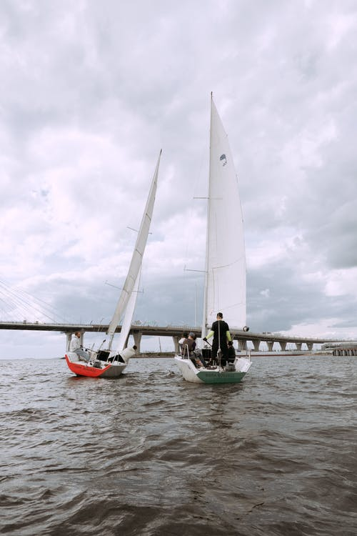 White Sail Boat on Body of Water Under Cloudy Sky