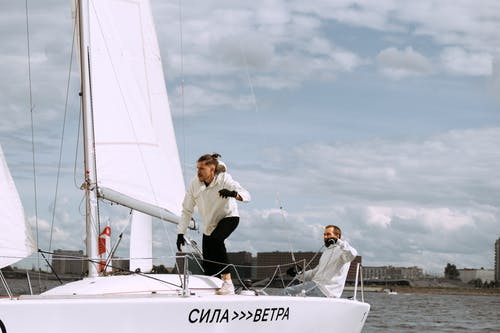 Man in White Dress Shirt and Black Pants Standing on White Boat