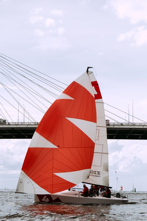 White and Red Sail Boat on Water
