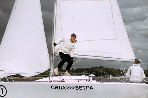 Man in White Shirt and Black Pants on White Boat