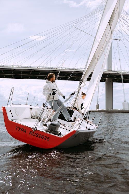 Uomo In Camicia Di Vestito Bianca Che Sta Sulla Barca Rossa E Bianca Sull'acqua