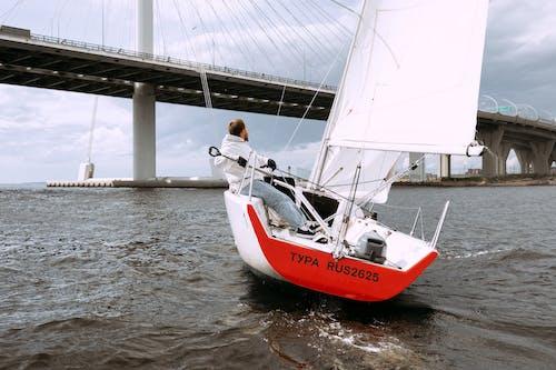 Uomo In Camicia Bianca E Pantaloni Neri Che Si Siede Sulla Barca Rossa E Bianca