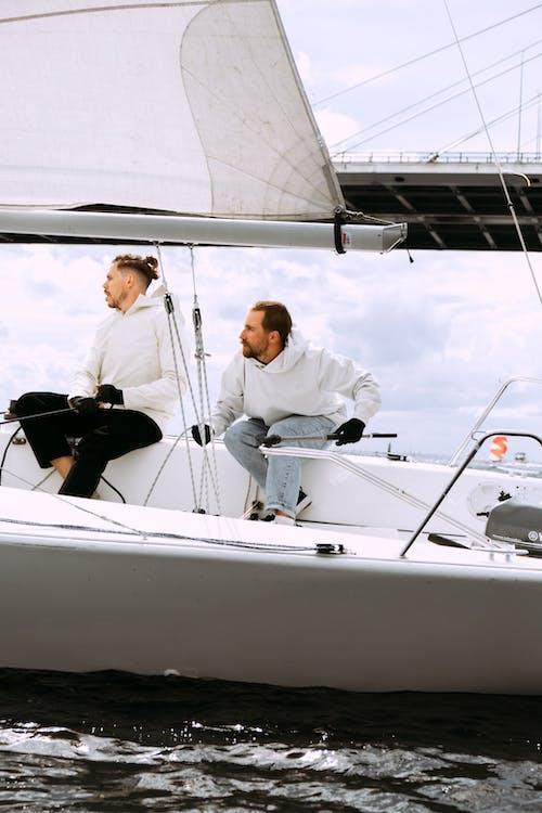 Uomo In Camicia Bianca E Pantaloni Neri Che Si Siede Sulla Barca Bianca