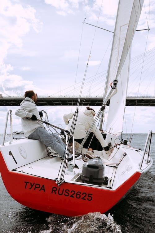 Uomo E Donna Che Guidano Sulla Barca Bianca E Rossa