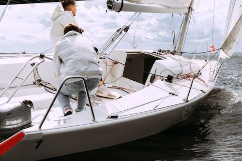 Uomo In Camicia Di Vestito Bianca Che Si Siede Sulla Barca Bianca E Marrone