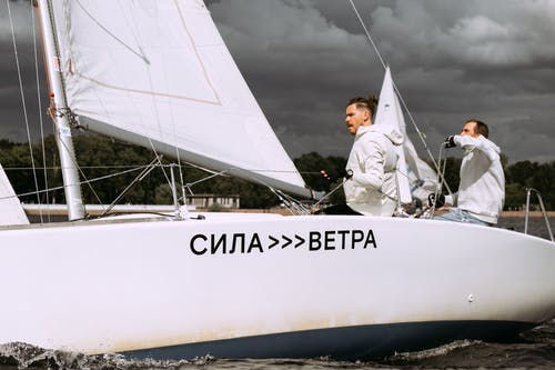 Mann Im Weißen Langarmhemd Und In Der Schwarzen Hose, Die Auf Weißem Segelboot Sitzen