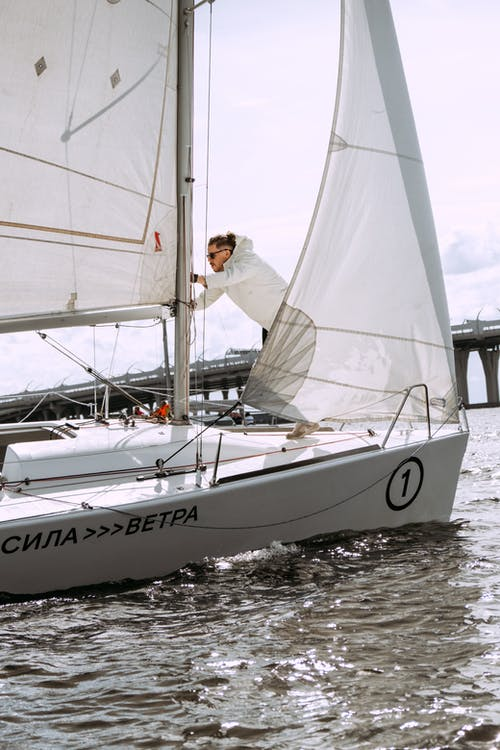Man in White T-shirt and Black Pants on White Sail Boat