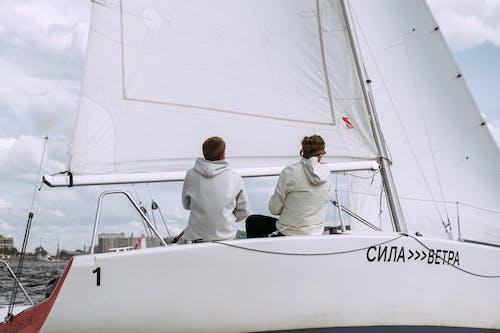 Uomo In Camicia Bianca E Pantaloni Neri Che Si Siedono Su Yacht Bianco