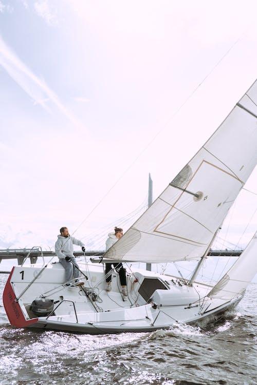 Man In Wit T Shirt En Zwarte Broek Staande Op Witte Zeilboot