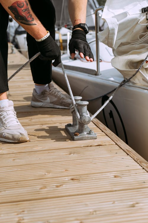 Person in Black Pants and White Nike Sneakers Standing on Brown Wooden Dock