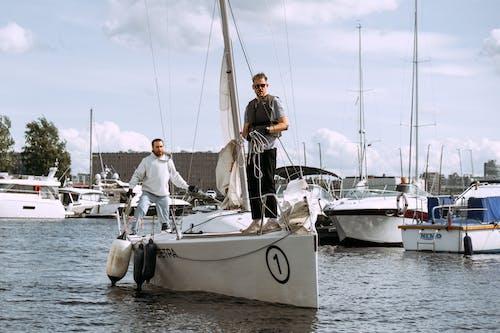 Mann Im Schwarzen T Shirt Und In Der Schwarzen Hose, Die Auf Weißem Segelboot Sitzen