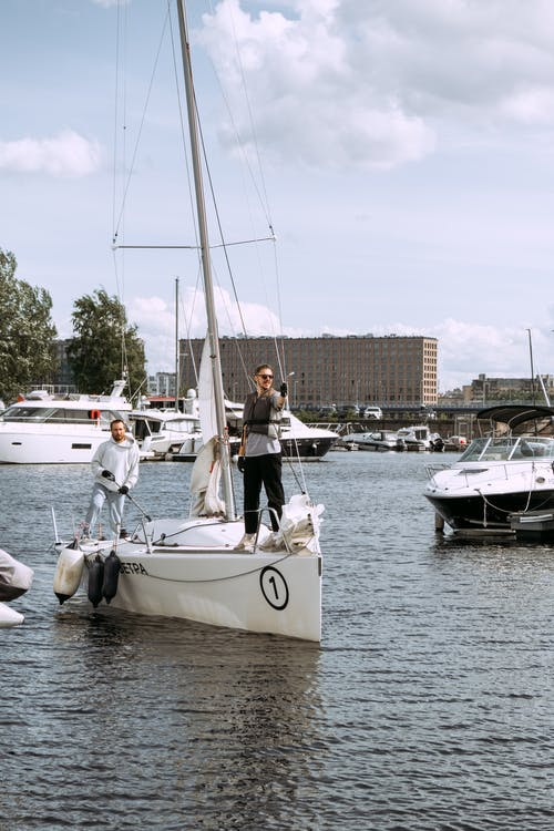 People Riding on White Sail Boat on Body of Water