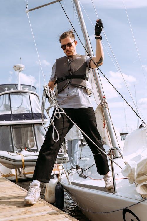 Mann In Der Schwarzen Und Weißen Jacke Und In Den Blauen Jeans, Die Auf Weißem Boot Stehen