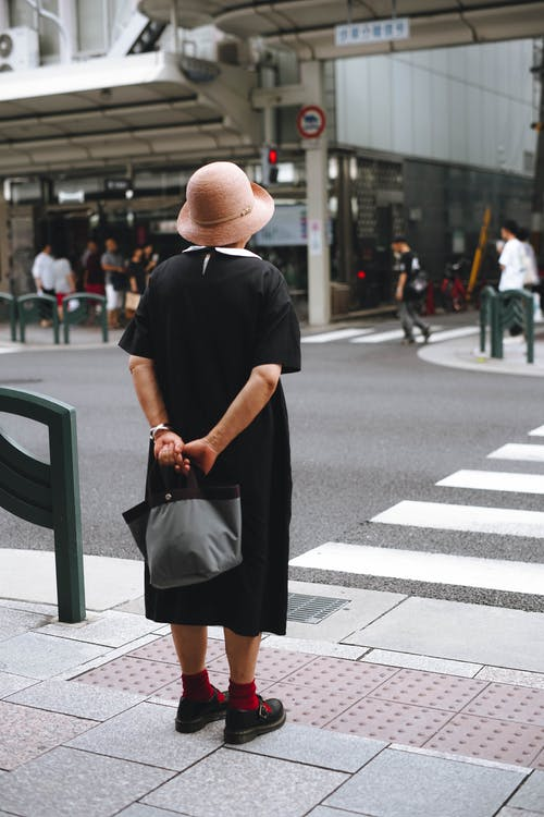 Woman in Black Dress and Brown Fedora Hat Standing on Pedestrian Lane