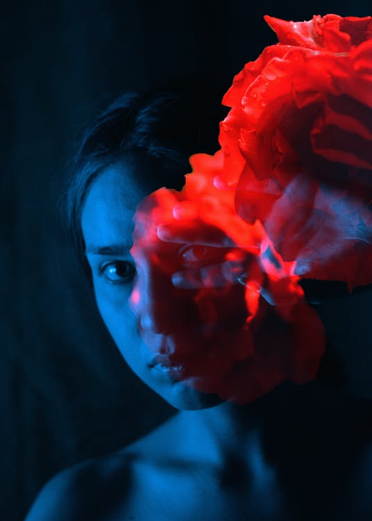Focused woman in bright neon smoke in evening