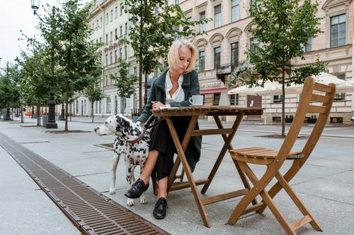 Woman in White and Black Dalmatian Dog Sitting on Brown Wooden Chair