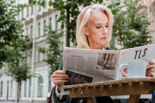 Woman Reading Newspaper on Brown Wooden Bench