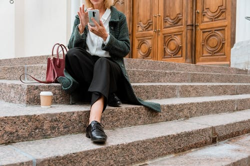 Woman in Gray Sweater and Black Skirt Sitting on Concrete Stairs