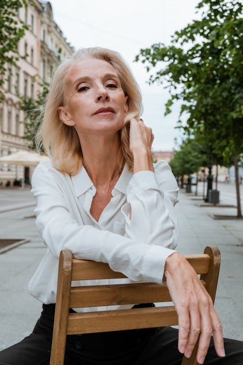 Woman in White Dress Shirt Sitting on Brown Wooden Chair
