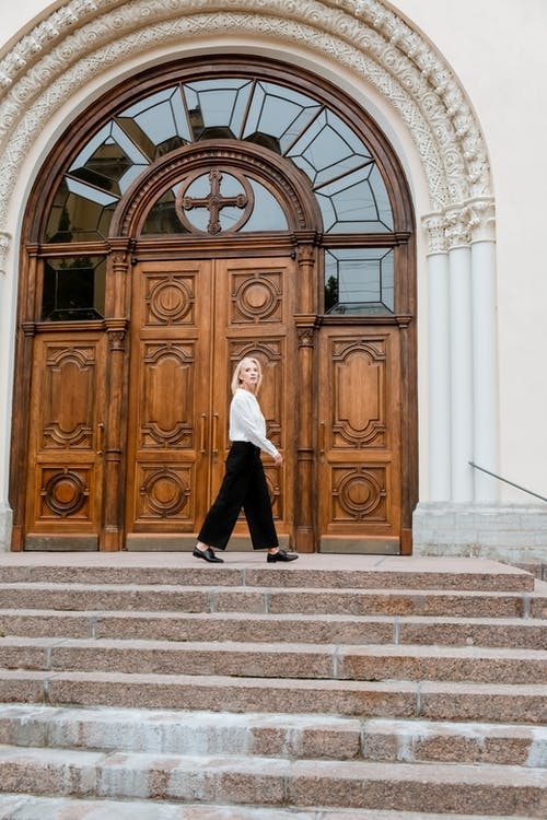 Woman in White Long Sleeve Shirt and Black Pants Standing Near Brown Wooden Door