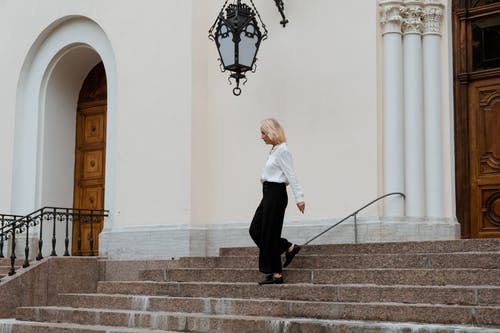 Woman in White Long Sleeve Shirt and Black Pants Standing on Gray Concrete Stairs
