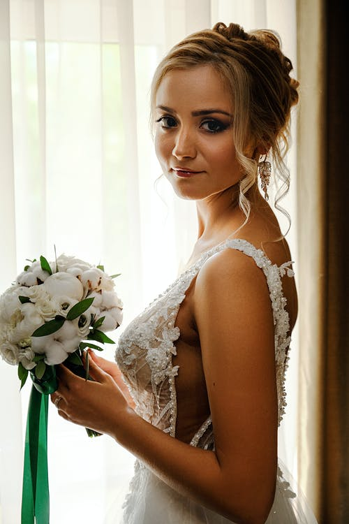 Side view of dreamy young bride in elegant white dress standing near window with white bouquet and looking at camera