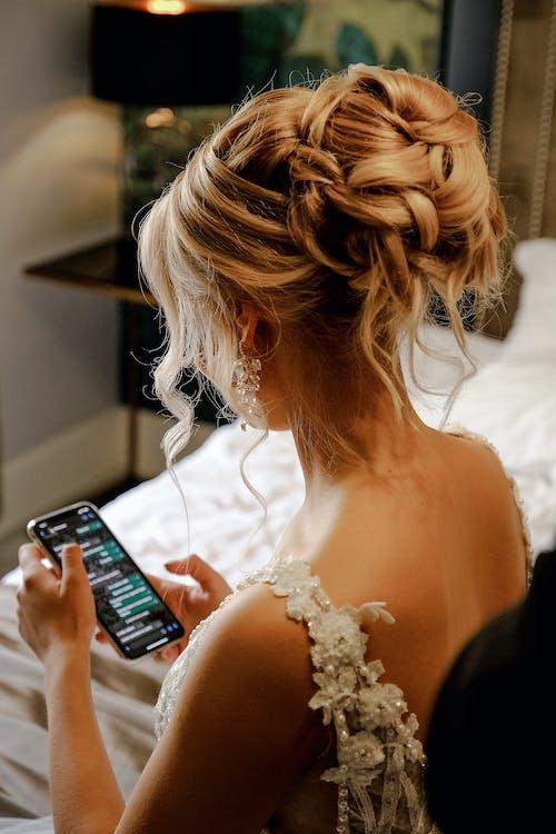 Unrecognizable bride browsing smartphone before wedding ceremony