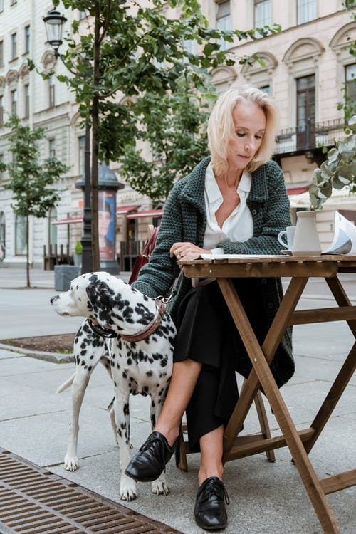 Woman in Black and White Polka Dot Dress Sitting on Brown Wooden Chair Beside Dalmatian Dog